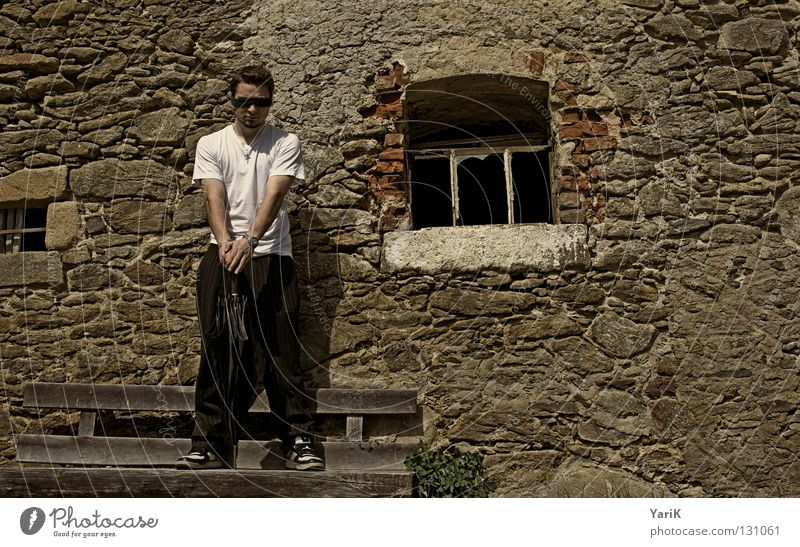 wartend Regenschirm Mann T-Shirt weiß schwarz braun steinig Wand Mauer Steinwand Steinmauer Putz Schlagschatten Fröhlichkeit heiter Lebensfreude Flucht flüchten