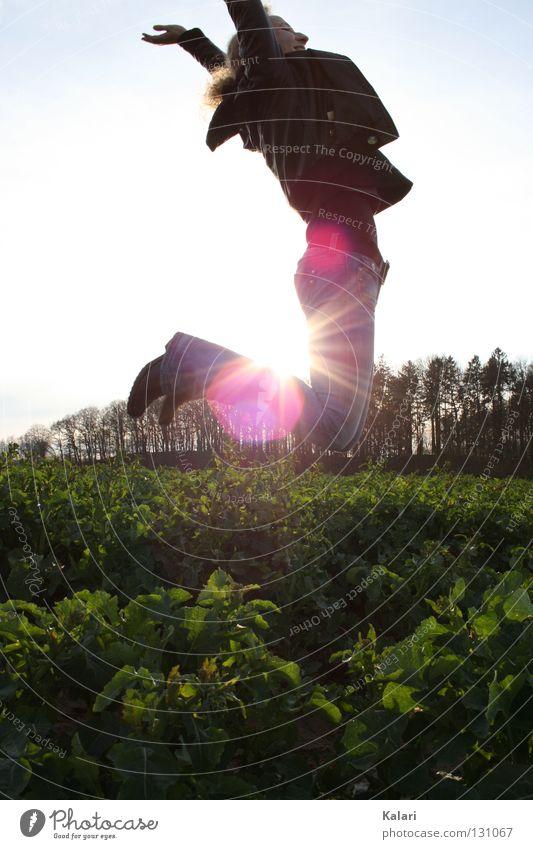 Höhenflug Frau kalt dunkel Feld grün Kohl springen Leichtigkeit Abendsonne Außenaufnahme Gegenlicht Sonnenuntergang Freude Frühling Himmel Klarheit blau frei