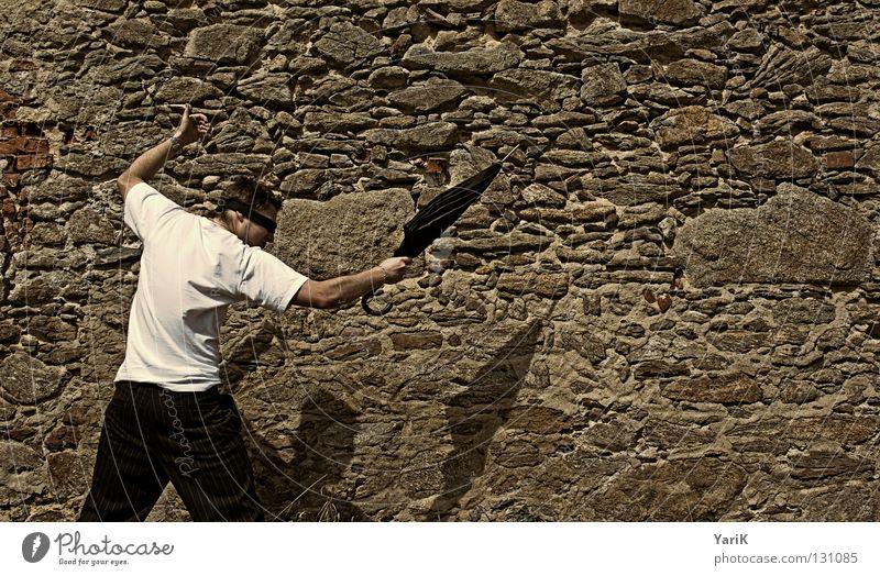 aus und vorbei springen Regenschirm Mann T-Shirt weiß schwarz braun steinig Wand Mauer Steinwand Steinmauer Putz Schlagschatten Fröhlichkeit heiter Lebensfreude