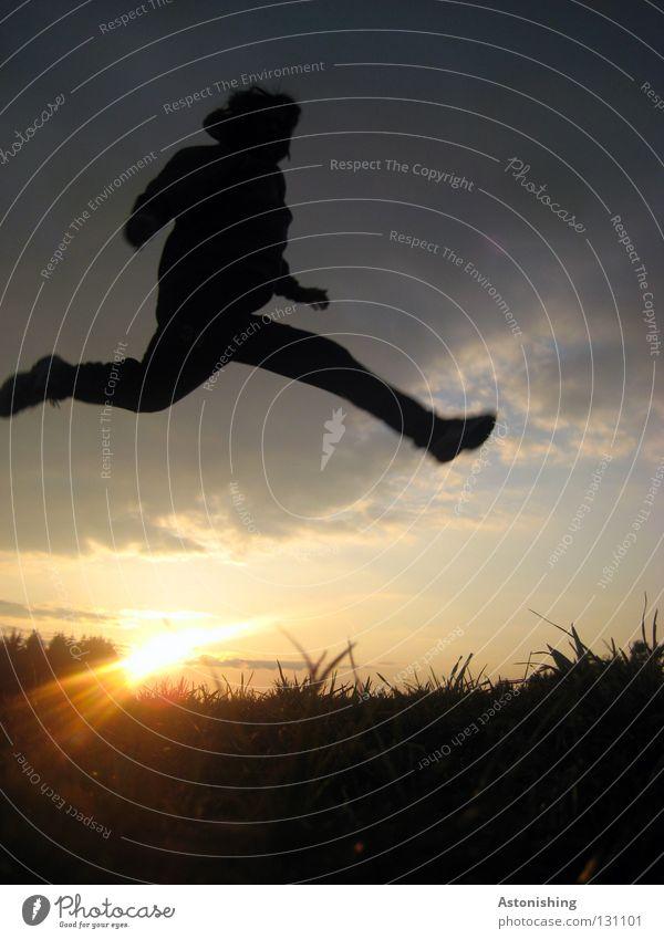 Sprung über die Sonne springen Mann Sonnenstrahlen Licht dunkel Wiese Wolken Sonnenuntergang Spielen Himmel Mensch Beleuchtung Lampe Schatten Kontrast Abend