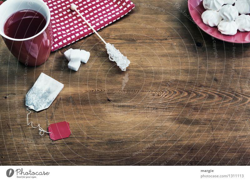 Roter Tee mit Zucker und Plätzchen auf einem Holztisch Kuchen Dessert Süßwaren Teebeutel Backwaren Getränk Heißgetränk Teller Tasse Serviette Lifestyle