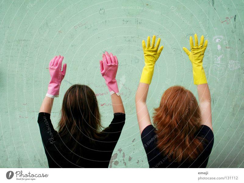 Zwei nicht identifizierbare Frauen mit Handschuhen Gummi rosa gelb knallig Rauschmittel türkis Wand beschrieben dreckig Reinigen edel skurril seltsam Karneval