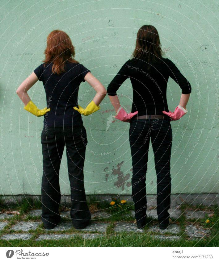 Zwei Frauen von hinten mit Gummihandschuhen Handschuhe rosa gelb knallig Rauschmittel türkis Wand beschrieben dreckig Reinigen edel skurril seltsam Karneval
