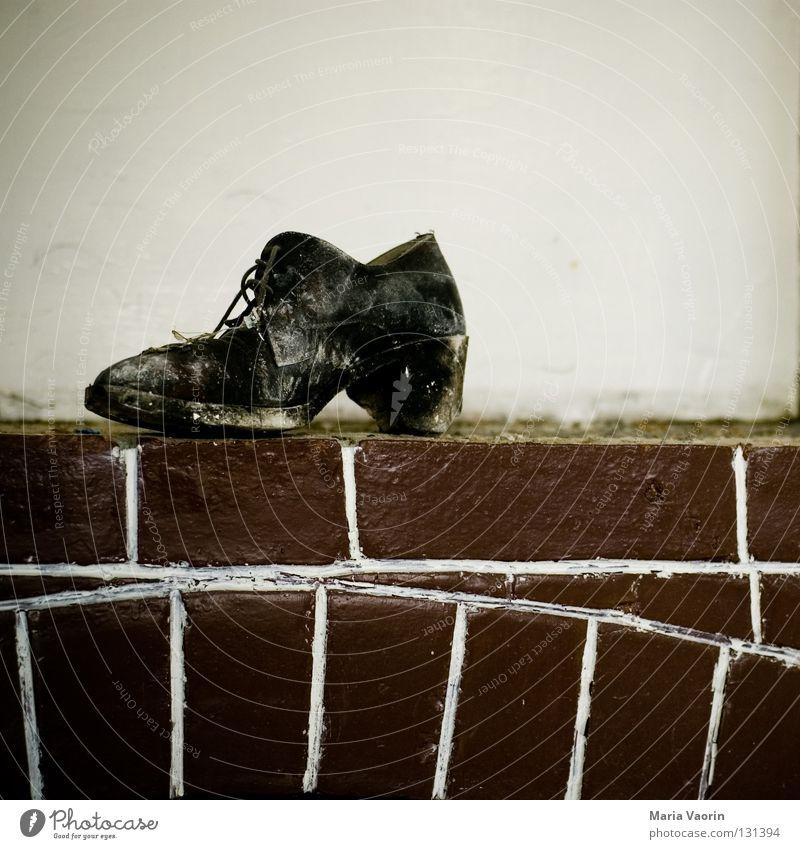 Wenn der Schuh drückt Schuhe unterwegs gehen treten binden Leder Lederschuhe Stoff dreckig Dinge gebraucht trist Ödland Kamin Backstein Schuhbänder Schuhsohle