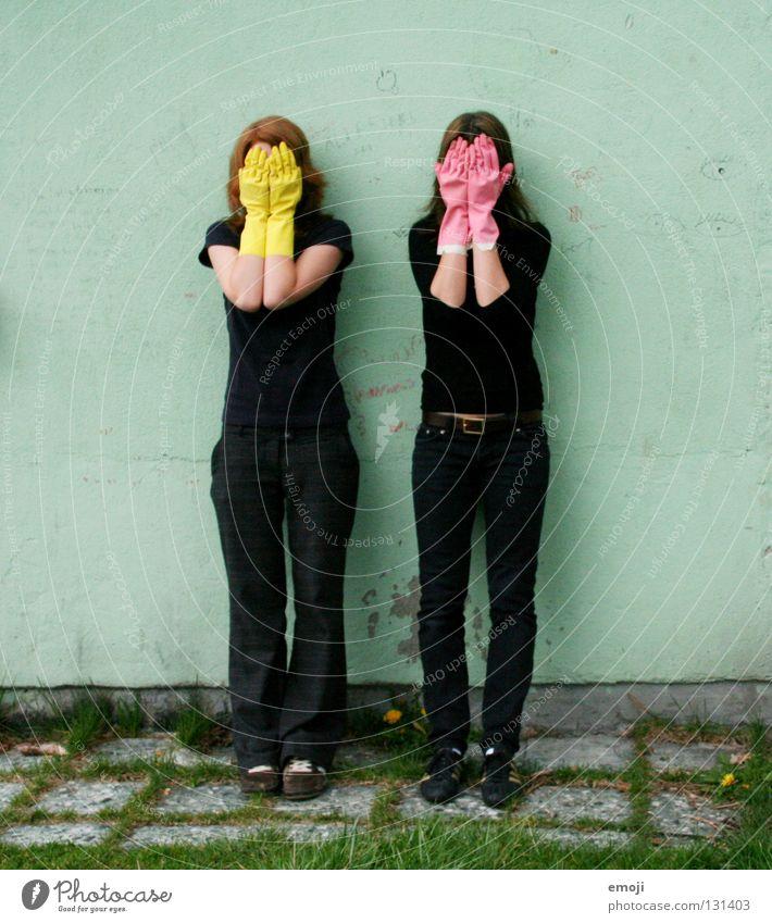 zwei Frauen verstecken sich hinter Gummihandschuhen Handschuhe rosa gelb knallig Rauschmittel türkis Wand beschrieben dreckig Reinigen edel skurril seltsam