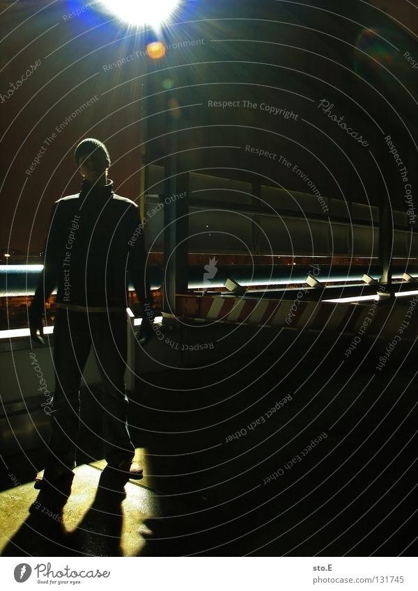 dark | standing in the light Mensch schwarz Ferne kalt dunkel Metall Lampe Beleuchtung glänzend Perspektive stehen Körperhaltung Aussicht Mütze Verkehrswege