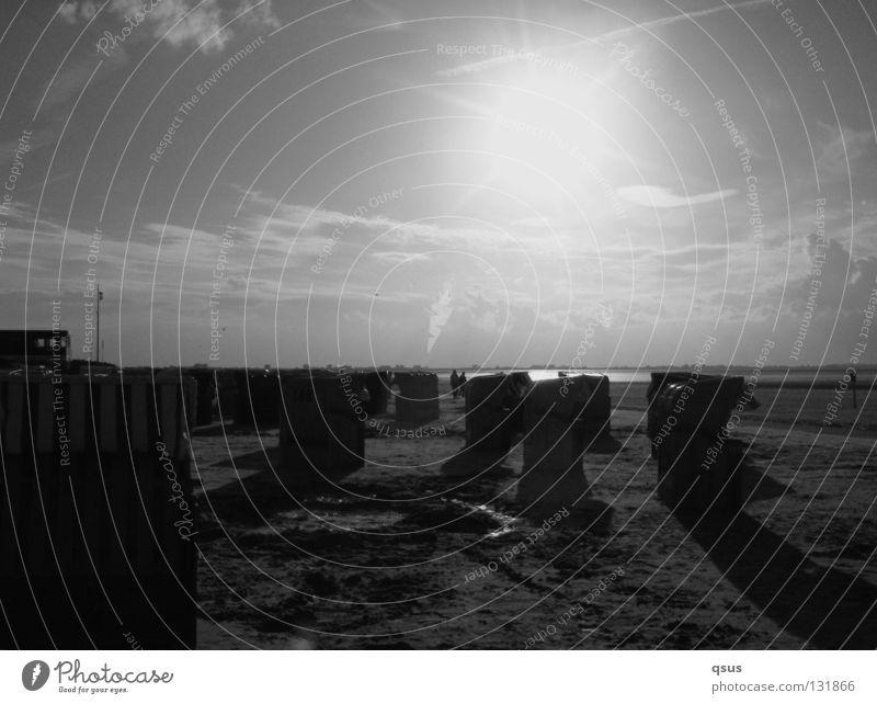 Strandkörbe Nachmittag Wolken erleuchten Strandkorb dunkel Schatten nass flach Meer Licht Gegenlicht Einsamkeit Sandburg kalt ruhig entvölkert Schwarzweißfoto