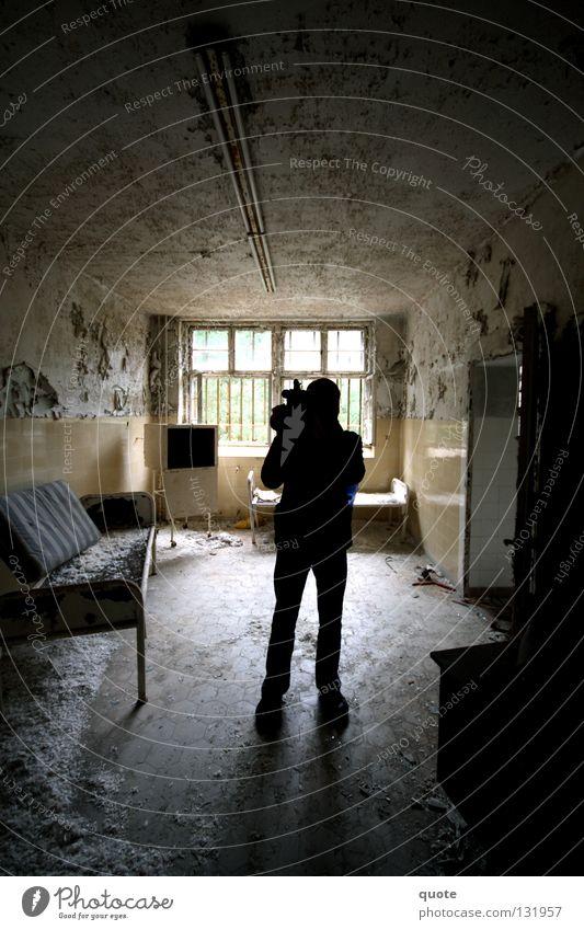 Kameramann Mann schwarz Fenster Graffiti Raum Bett Fernsehen kaputt Feder Fotokamera Müll verfallen Ruine Zerstörung Schrank