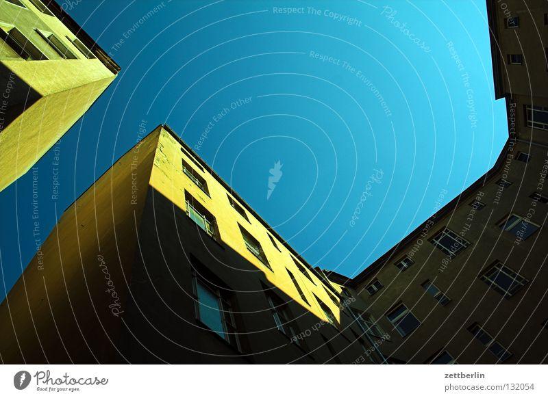 Hinterhof again Lichthof Stadthaus Brandmauer Mauer eng Haus Froschperspektive hinterhaus Himmel Plattenbau Ferne blau Perspektive mietspiegel