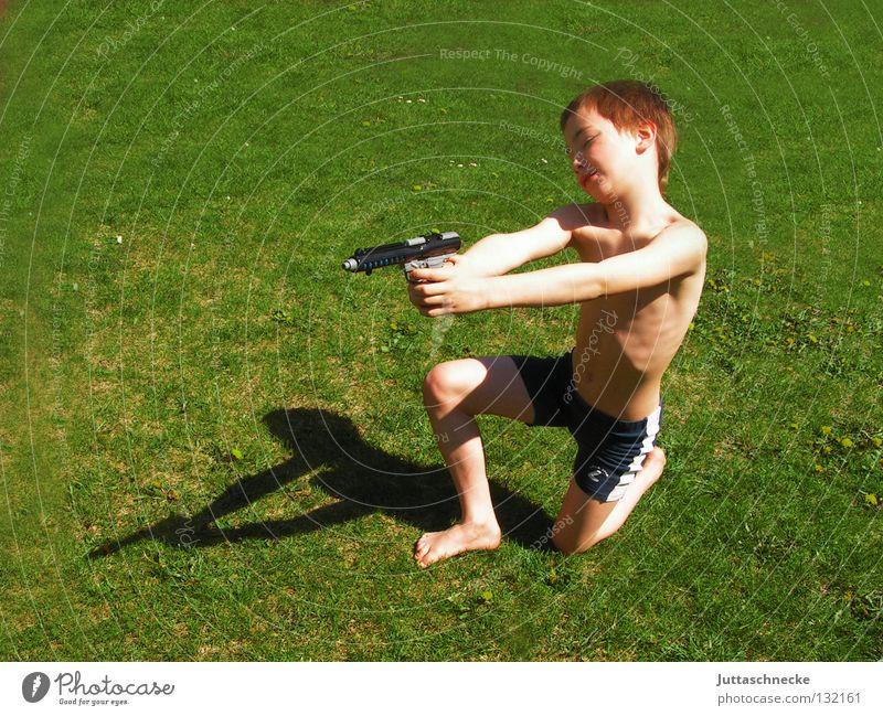 Peng, du bist nass! Junge Kind Pistole Wasserpistole Spielzeug Spielzeugwaffen Spielen Gras Wiese Sommer grün Cowboy schießen Waffe Treffer Lausbuben Lausejunge
