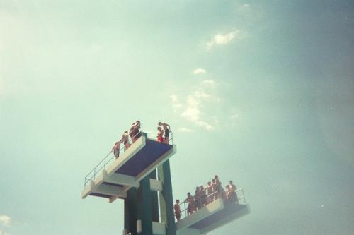 Viele Junge Menschen auf einem Sprungturm vor blauem Himmel Schwimmbad Freiheit Sommer Sonne Sport Kindheit Menschengruppe Wasser Schönes Wetter Treppe Badehose