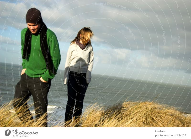 Wir zwei Mann Frau Meer Wolken schlechtes Wetter Strand grün grau Pullover Schal Mütze Bewegung gehen Gras Wind Trennung kalt Hand Hose dunkel Winter Mensch