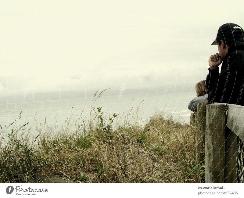 und wir waren zuhause. Mann Frau grün braun verwaschen trist Wolken Junger Mann Junge Frau Gras Hügel Meer verpackt kalt Denken Baseballmütze Regenjacke Wind