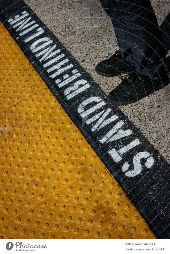 STAND BEHIND LINE Mensch schwarz gelb Fuß Schuhe Linie Beine warten Eisenbahn USA stehen Schriftzeichen Bodenbelag Buchstaben stoppen Hinweisschild