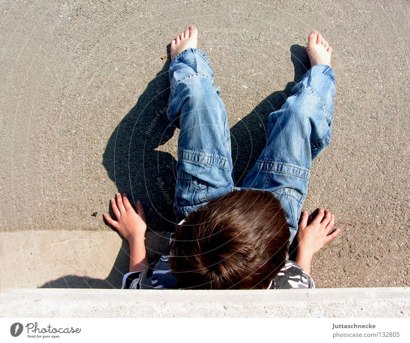 Warten auf Godot Kind Junge hocken Mauer Wand Beton anlehnen Vogelperspektive Pause Erholung Sonntag Barfuß lümmeln Parkplatz Langeweile Frieden boy boys
