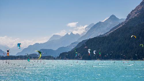 Berglandschaft mit vielen Kitesurfern und Windsurfern, die sich in einem See bewegen. Sie nutzen den Wind, um ihre Bretter auf dem Wasser zu bewegen. Berge sind als Hintergrund an einem sonnigen Tag.