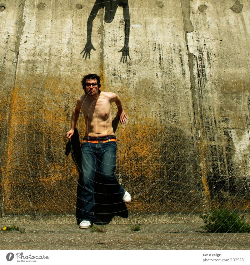 THE WALL | TURN TAIL AND FLEE Mensch Mann Jugendliche alt Freude Wand Gras Mauer lustig Angst Glas Beton Symbole & Metaphern Jeanshose festhalten Zeichen