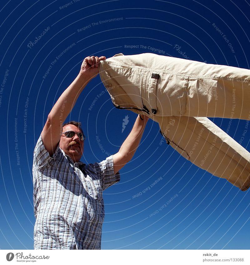 windhose Strand nass Hose Wellen trocknen Wind Tornado hochhalten ausbreiten Shorts Mann Lanzarote Meer Geplätscher lüften Luft blasen dick Sonnenbrille
