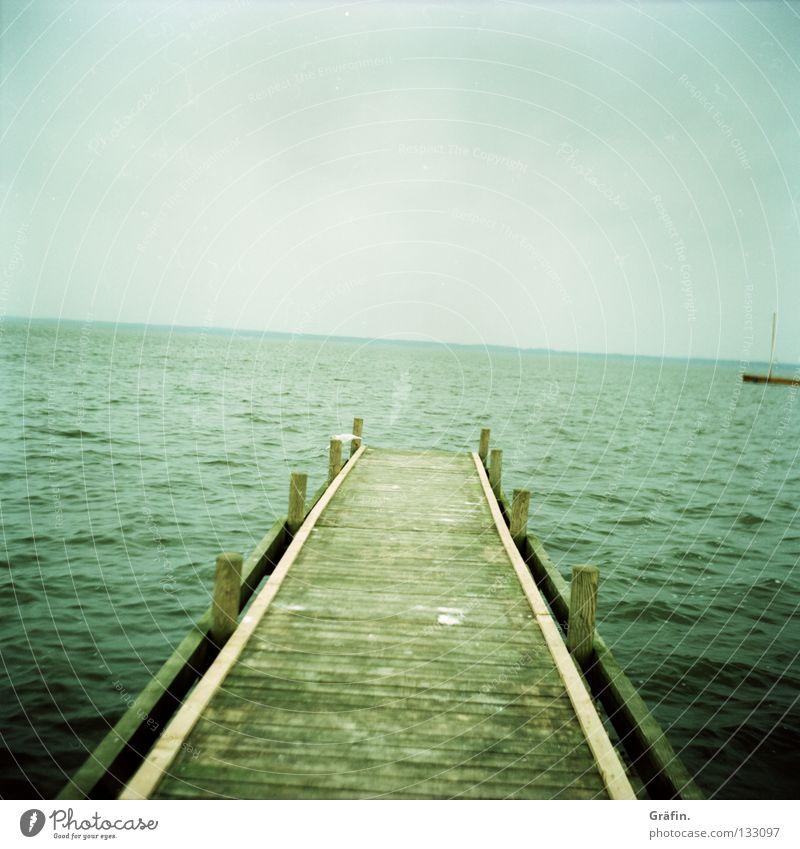 es kippt See Mittelformat Meer Teich Gewässer Wellen nass Steg Möwe Vogel Holz Anlegestelle grün Umweltschutz Unendlichkeit Wasserfahrzeug Ekel grau Wolken