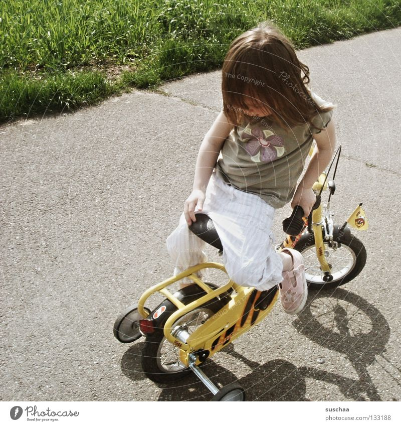 stuntkid II Asphalt Kind Kleinkind Mädchen klein Fahrradfahren Stunt Freestyle verkehrt Mut frech gefährlich verwegen Spielen Extremsport Straße sitzen