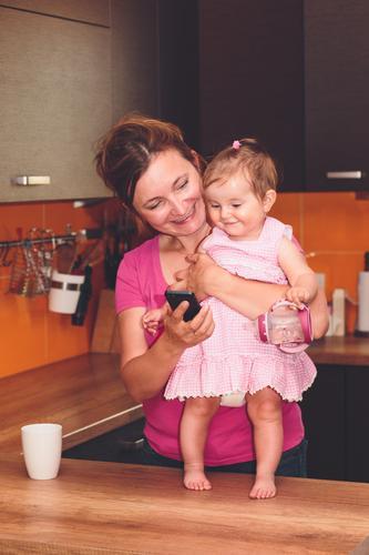 Frau, die ihren kleinen Tochtervideoanruf mit Großmutter zeigt Lifestyle Freude Glück Küche Baby Kleinkind Mädchen Erwachsene Eltern Mutter