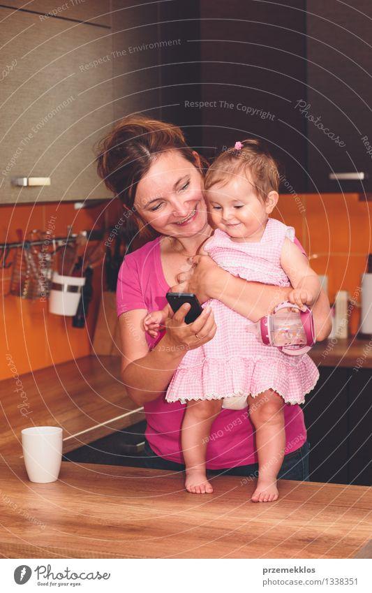 Mensch Frau Freude Mädchen Erwachsene Glück Familie & Verwandtschaft klein Lifestyle Lächeln Baby niedlich Küche Telefon Mutter Kleinkind