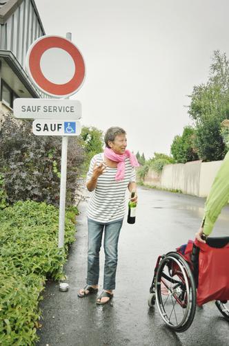 on the road again | sauf service Straße Frau Rollstuhl Französisch Frankreich Wortspiel Alkohol Flasche Wein Verkehrsschild Gehbehinderung Abholservice
