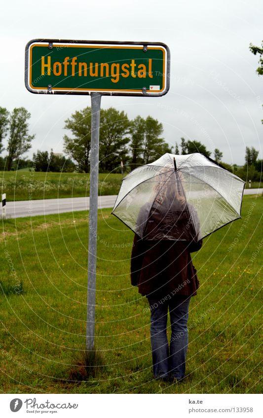 es gibt HOFFNUNG Hoffnung Regenschirm Ortsschild grün Außenaufnahme Frau durchsichtig Gras Straßenrand Baum graue Wolken trist nass Trauer Götter stehen