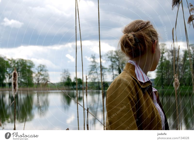 abneigung See Frau feminin Jugendliche Spiegel Baum Sträucher Park Binnensee Schilfrohr Wolken trüb Physik Frühling grün Bluse Hemd Dutt Pferdeschwanz Zopf
