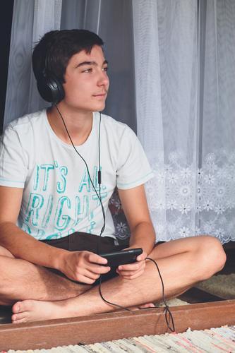 Junge, der an der Terrassentür sitzt und Musik hört Lifestyle Freude Erholung Freizeit & Hobby Sommer Telefon Junger Mann Jugendliche 13-18 Jahre Tür hören