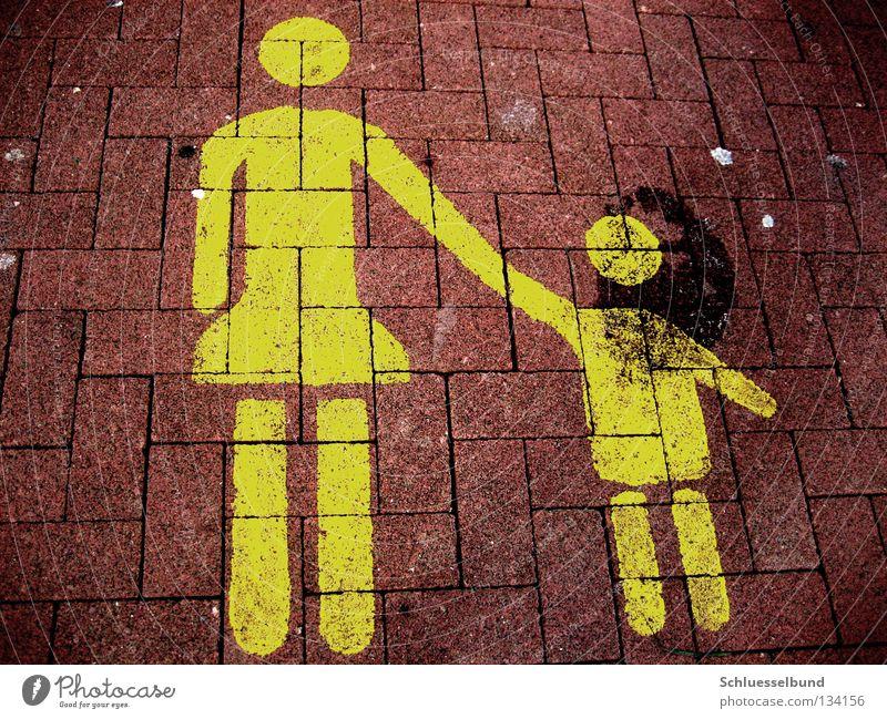 Mutter mit Kind Parkplatz Erwachsene Arme Beine Verkehrswege Stein dunkel gelb rot schwarz Fahrbahnmarkierung Steinboden berühren Farbfoto mehrfarbig