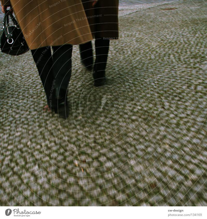 DOLCE & GABBANA Frau Mann Schuhe bodennah Mantel Hose Grauwert Winter Herbst trist grau Unschärfe Bodenbelag Muster Ehepaar Kopfsteinpflaster Bewegungsunschärfe