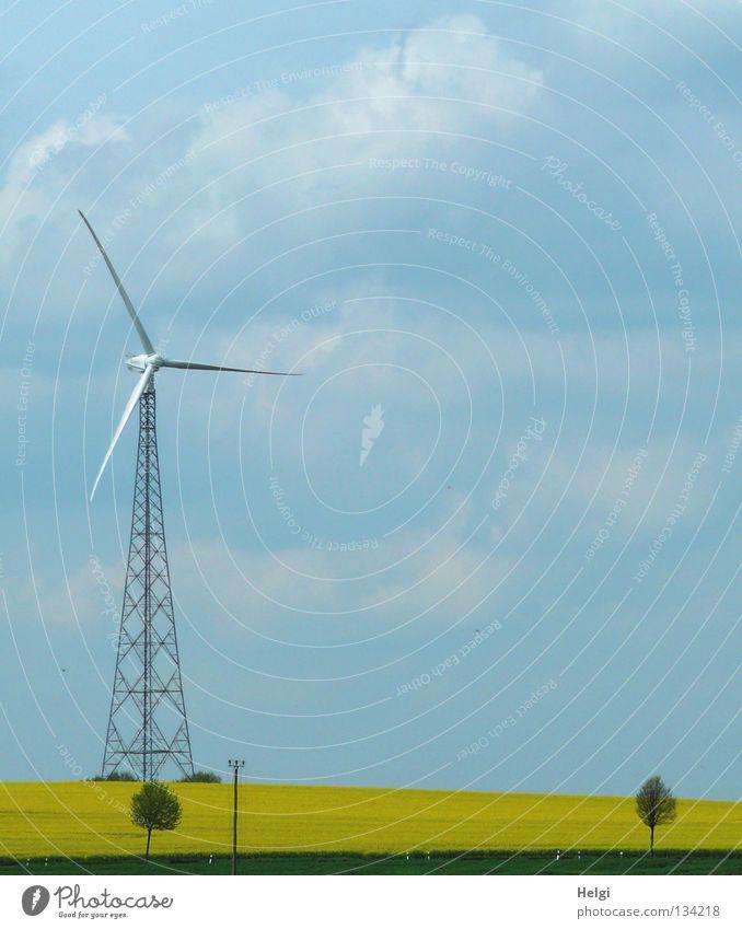Windkraftanlage vor blauem Himmel mit Wolken an einem Rapsfeld streben Länge quer emporragend groß rotieren drehen Elektrizität Erneuerbare Energie