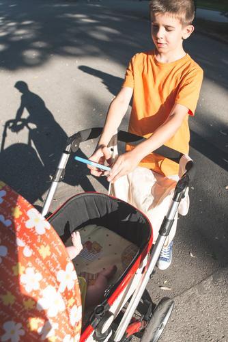 Kind mit dem Smartphone, der ein Foto des Babys macht Natur Sommer Sonne Junge Glück klein Zusammensein Park Lächeln Fotografie Grafik u. Illustration Telefon