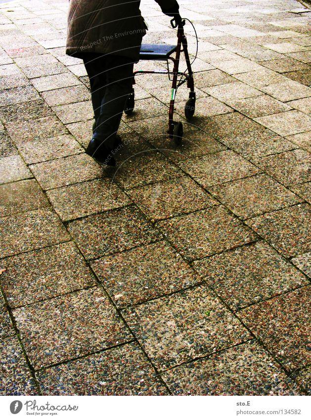 auf der zielgeraden Frau Senior Bewegung Stein gehen laufen Vergänglichkeit Verkehrswege Kopfsteinpflaster diagonal Rolle Gehhilfe Pflastersteine Korb parallel