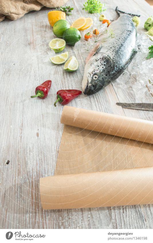 Rohe Lachsfische in Eis und Gemüse Meeresfrüchte Abendessen Tisch Koch Papier frisch lecker rot weiß Fisch Lebensmittel roh Zitrone Backpapier Messer hölzern