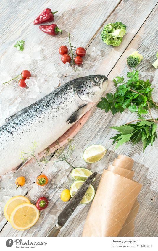 Rohe Lachsfische im Eis Meeresfrüchte Gemüse Abendessen Tisch Koch Papier frisch lecker rot weiß Fisch Lebensmittel roh Zitrone Backpapier Messer hölzern Tomate