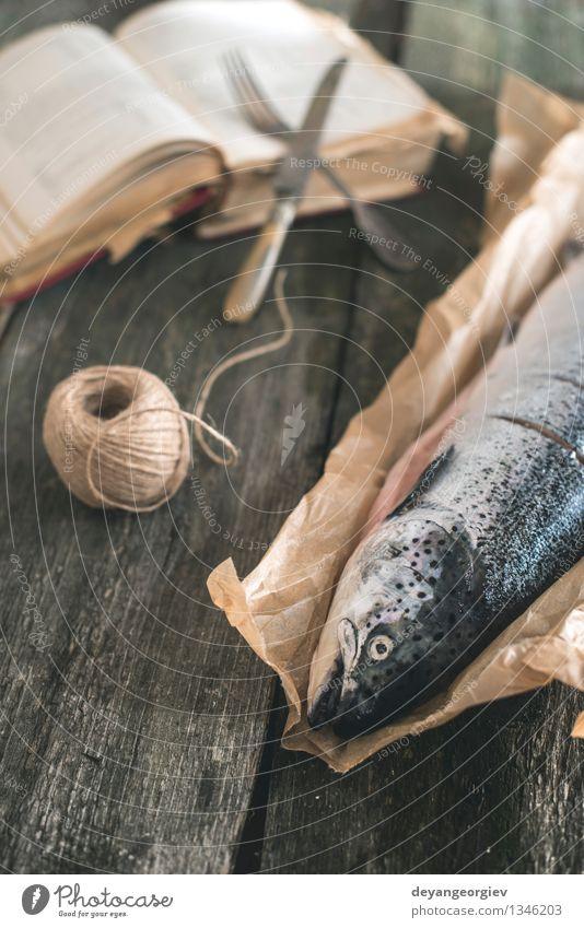 Rohe Lachsfische auf Weinleseholztisch Meeresfrüchte Mittagessen Gabel Tisch Seil Buch alt dunkel frisch Fisch altehrwürdig roh Lebensmittel Kochbuch
