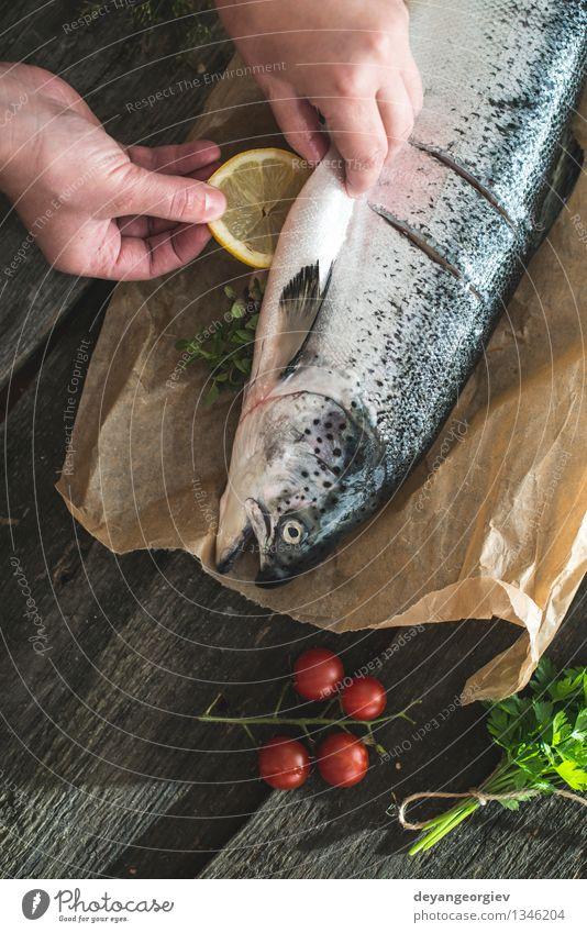 Vorbereiten ganze Lachs Fisch zum Kochen. dunkel schwarz frisch Tisch Kochen & Garen & Backen Papier Seil Gemüse lecker Mahlzeit Abendessen Tomate Zitrone roh