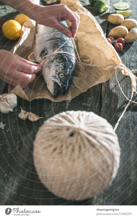 Ein Seil an Fische zum Grillen binden dunkel schwarz frisch Tisch Kochen & Garen & Backen Papier Gemüse lecker Mahlzeit Abendessen Tomate Zitrone roh Zutaten