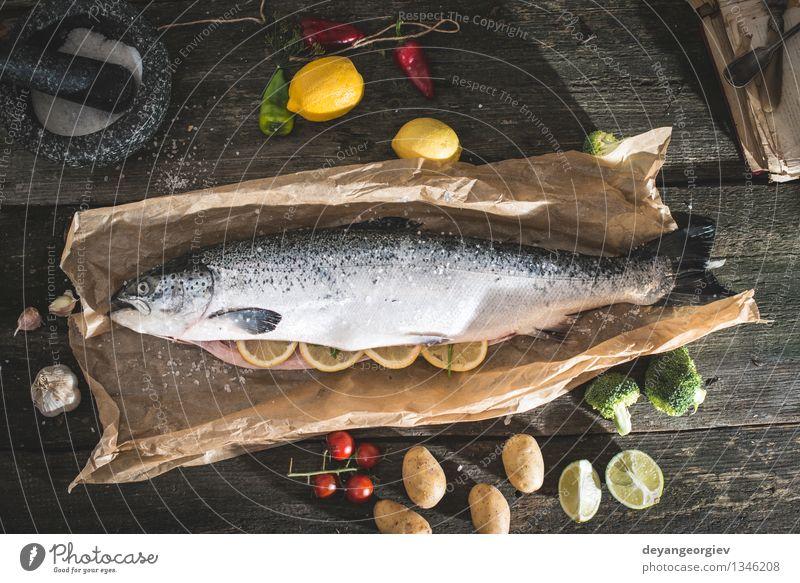 Bereiten ganze Lachs Fisch zum Kochen dunkel schwarz frisch Tisch Kochen & Garen & Backen Papier Seil Gemüse lecker Mahlzeit Abendessen Tomate Zitrone roh