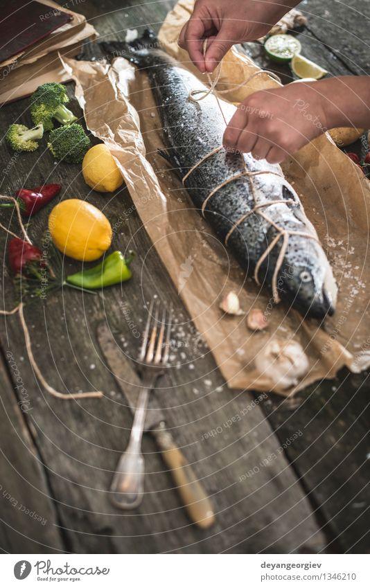 Ein Seil an Fische zum Grillen binden Meeresfrüchte Gemüse Abendessen Tisch Koch Hand Papier dunkel frisch lecker schwarz kochen & garen roh Zutaten Mahlzeit
