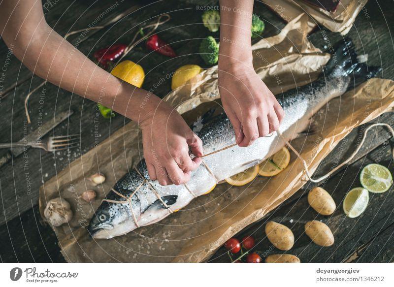 Ein Seil an Fische zum Grillen binden Hand dunkel schwarz frisch Tisch Kochen & Garen & Backen Papier Gemüse lecker Mahlzeit Abendessen Tomate Zitrone roh