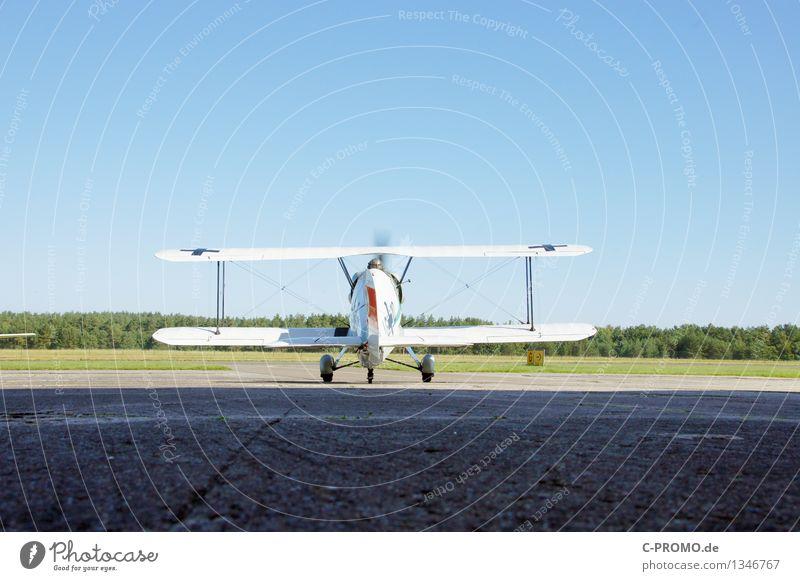 Doppeldeckerstart Landschaft Luft Himmel Wolkenloser Himmel Wald Luftverkehr Flugzeug Flughafen Landebahn Flugzeuglandung Flugzeugstart blau Abheben Propeller