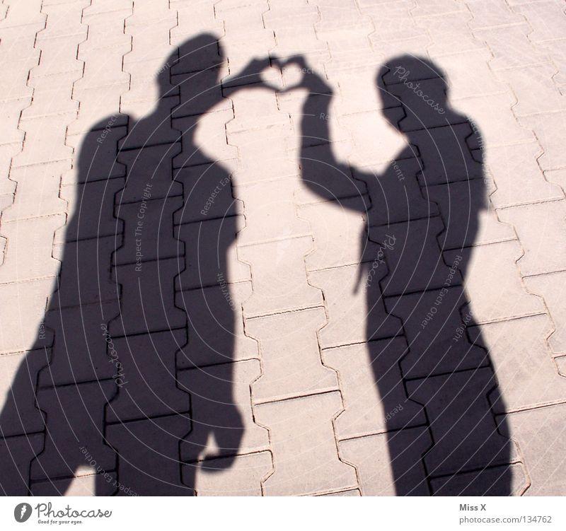 Schattenseiten der Liebe Frau Mensch Hand schwarz Erwachsene Straße grau Stein Beine Freundschaft Herz Asphalt Kies unterwegs Schattenspiel