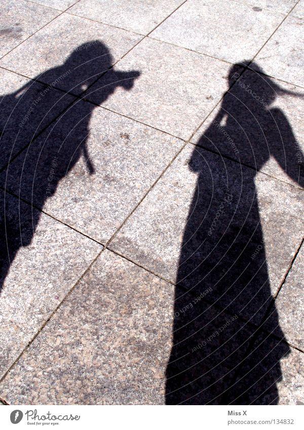 Scheiß Paparazzi Farbfoto Schwarzweißfoto Außenaufnahme Schatten Silhouette Mensch Frau Erwachsene Mann Beine Straße grau schwarz Asphalt steinig unterwegs