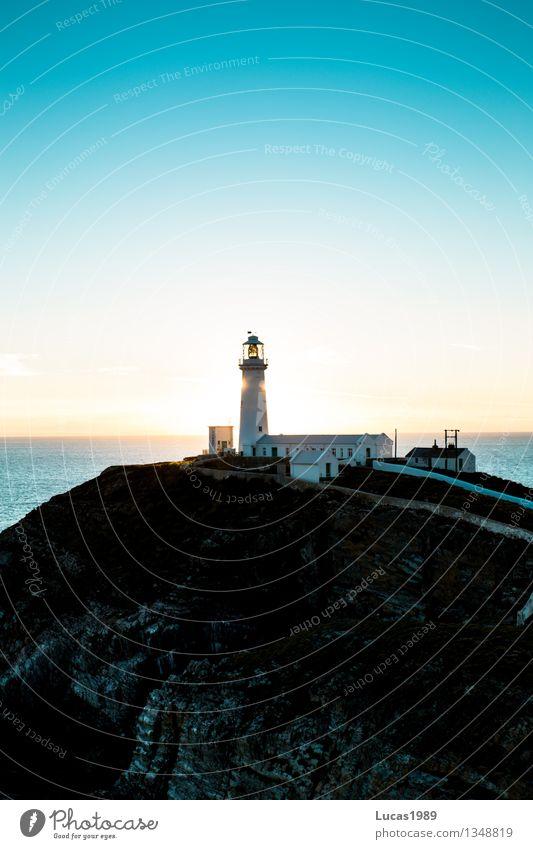 Leuchtturm im Sonnenaufgang Ferien & Urlaub & Reisen blau Meer Landschaft Ferne Strand Umwelt Architektur Küste Gebäude Freiheit Felsen Tourismus Wellen Insel