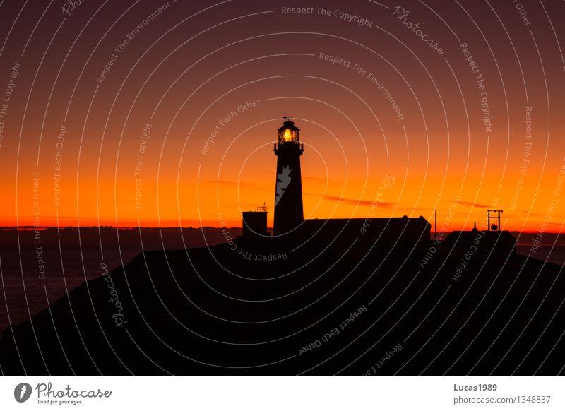 das Licht das leitet Nachthimmel Fischerdorf Hafenstadt Turm Leuchtturm dunkel orange rot schwarz leuchten Silhouette Wegweiser Meer Küste Farbfoto