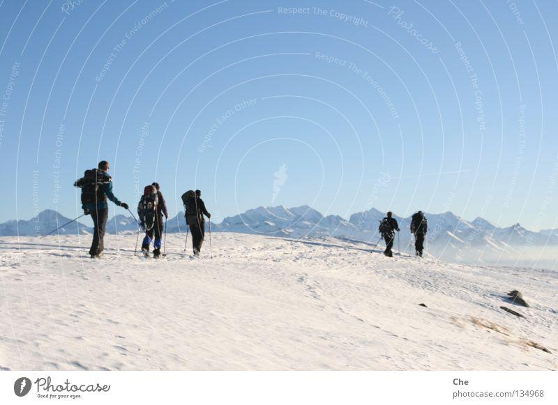 Unterwegs im Nirgendwo Ferien & Urlaub & Reisen Schneeschuhe Schweiz Bergkette Winter wandern Mann Wanderstock Einsamkeit hart Ferne verloren Aussicht kalt weiß