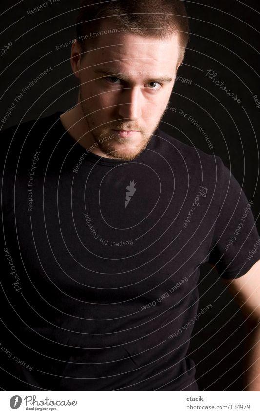 young man portrait Mensch Porträt Körperhaltung Mann maskulin Anschnitt Bildausschnitt Blick in die Kamera T-Shirt Vor dunklem Hintergrund Low Key ernst grimmig